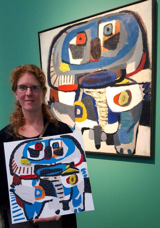 Jofke toont de in het van Abbemuseum de Taktila™ reproductie van 'De vierkante man van Karel Appel'. op de achtergrond hangt het origineel.